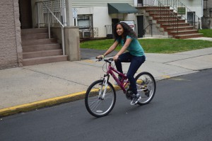 A young woman bicycling in New Brunswick, NJ.