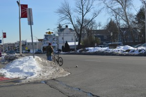Identifying a place to store snow is an important consideration. This bicyclist is waiting on the street because the bus stop is covered with snow.